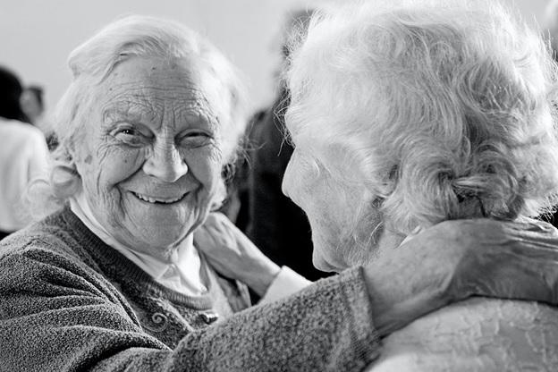 elderly women touching shoulders
