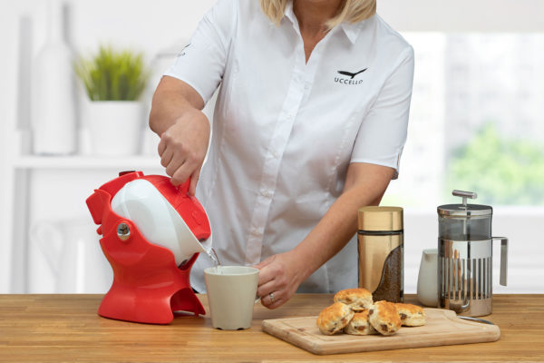 Lady using the tilt-to-pour action of the red and white Uccello Kettle